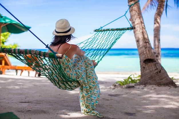 Jonge vrouw die in de hangmat op tropisch strand ligt