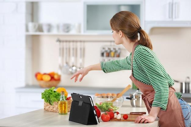 Jonge vrouw die in de keuken kookt