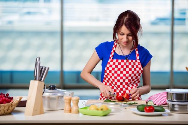Jonge vrouw die in de keuken werkt