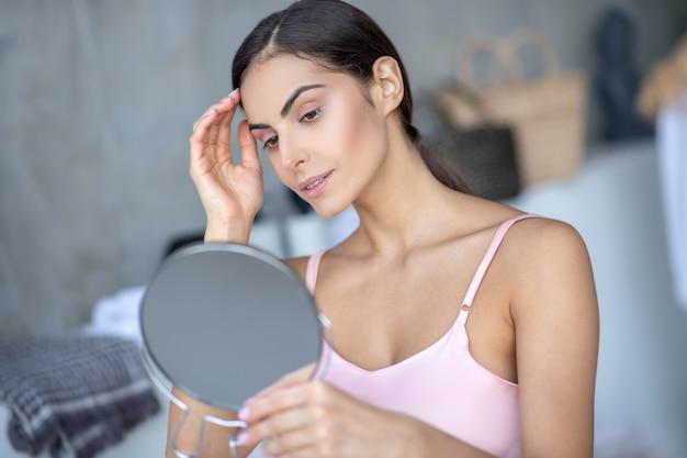 Jonge vrouw die in de spiegel in de badkamers kijkt