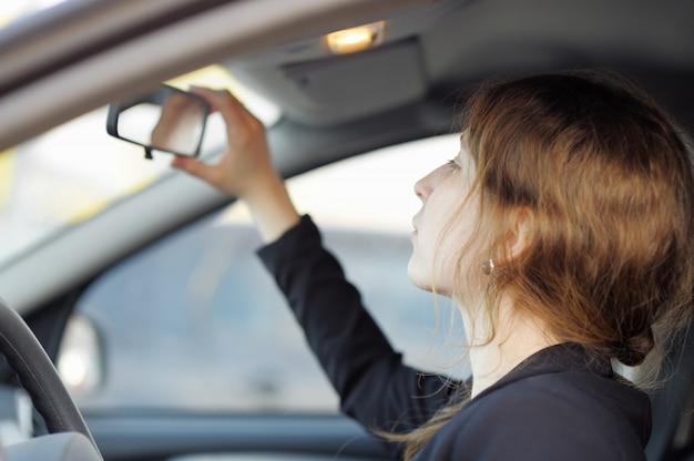 Jonge vrouw die in de spiegel in een auto dicht omhoog kijkt