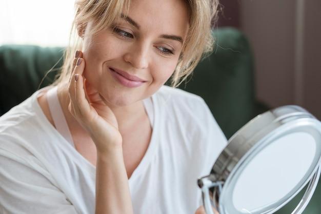 Jonge vrouw die in de spiegel kijkt