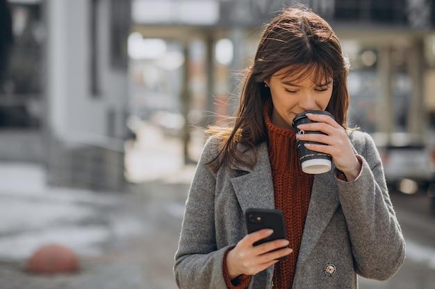 Jonge vrouw die in de straat loopt en koffie drinkt