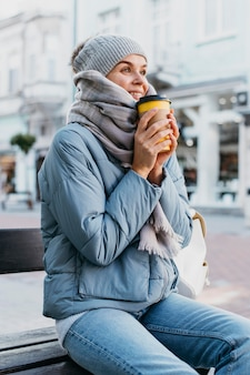 Jonge vrouw die in de winterkleren een kop van koffie houdt