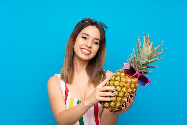 Jonge vrouw die in de zomervakantie over blauwe muur een ananas met zonnebril houdt