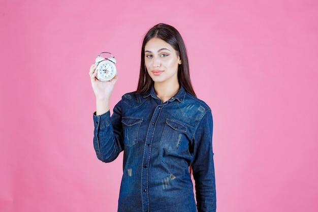 Jonge vrouw die in denimoverhemd een wekker houdt en bevordert