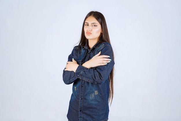 Jonge vrouw die in denimoverhemd handen kruist en koud voelt