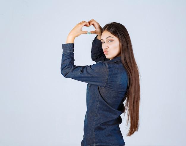 Jonge vrouw die in denimoverhemd liefde verzendt