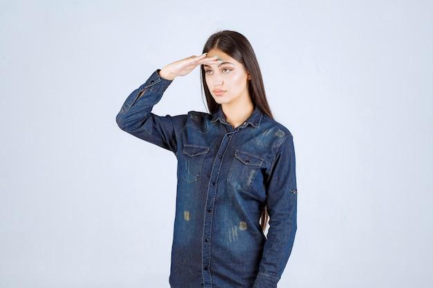 Jonge vrouw die in denimoverhemd militaire groet geeft
