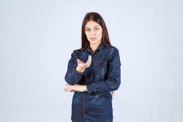 Jonge vrouw die in denimoverhemd naar de persoon voor haar richt