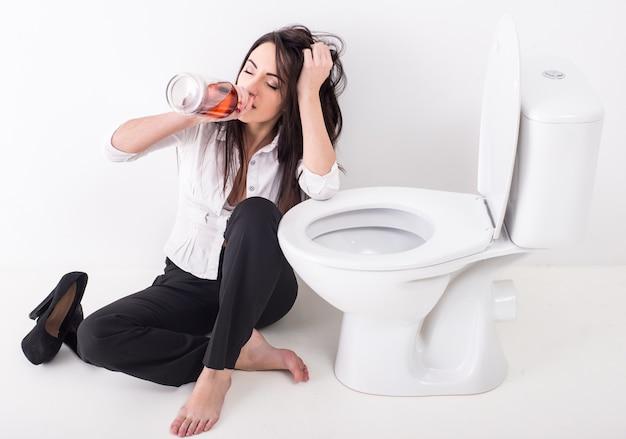 Jonge vrouw die in depressie alcohol in toilet drinkt.