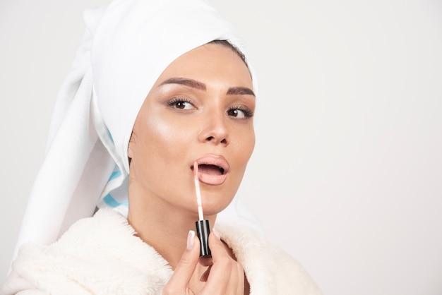 Jonge vrouw die in een badjas een lippenstift toepast