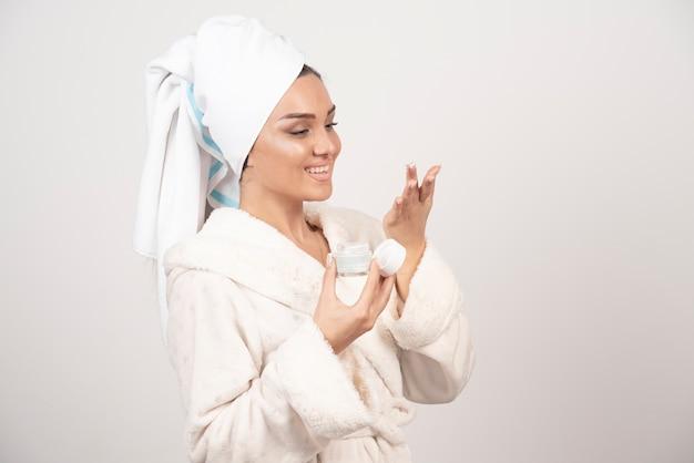 Jonge vrouw die in een badjas een room toepast