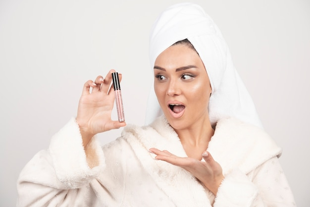 Jonge vrouw die in een badjas lippenstift bekijkt