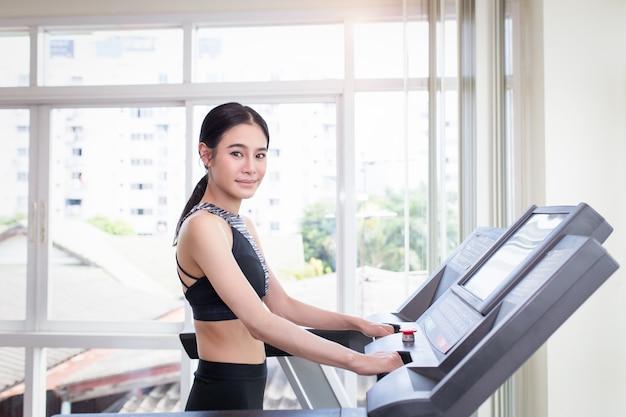 Jonge vrouw die in een gymnastiek uitwerkt