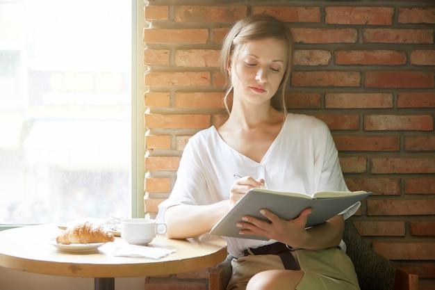 Jonge vrouw die in een planner bij de koffielijst schrijft in de ochtend