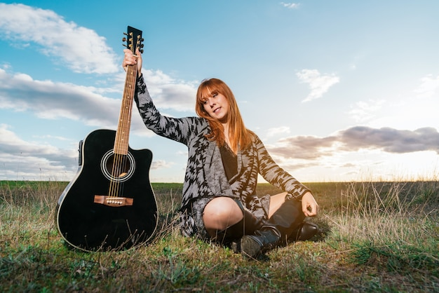 Jonge vrouw die in een veld zit en glimlacht terwijl ze naar een zwarte gitaar kijkt onder een hemel met wolken
