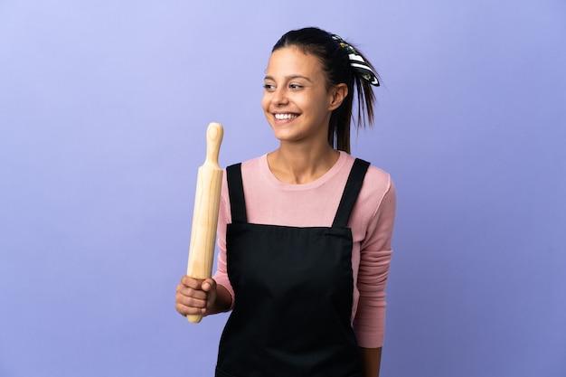 Jonge vrouw die in eenvormige chef-kok aan de kant kijkt en glimlacht