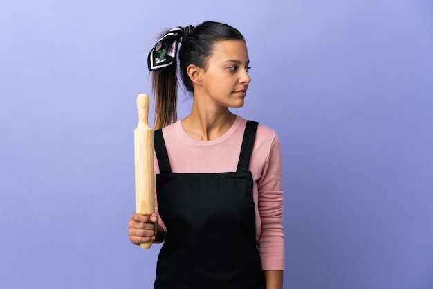 Jonge vrouw die in eenvormige chef-kok aan de kant kijkt