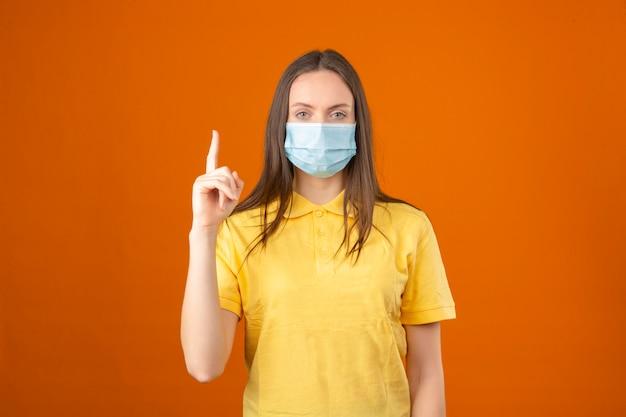 Jonge vrouw die in geel poloshirt en medisch beschermend masker omhoog wijzend vinger op oranje achtergrond bekijken