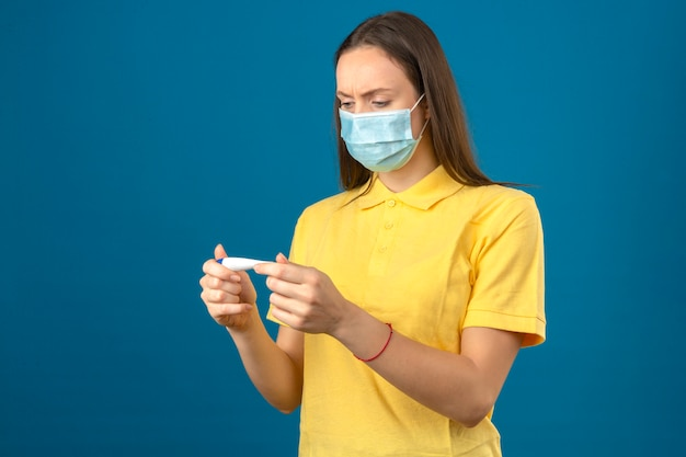 Jonge vrouw die in geel poloshirt en medisch beschermend masker thermometer met ernstig gezicht op geïsoleerde blauwe achtergrond bekijken