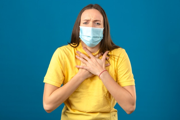 Jonge vrouw die in geel poloshirt en medisch beschermend masker ziek kijken hebbend pijn in haar borst die zich op blauwe achtergrond bevindt