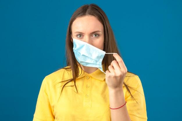 Jonge vrouw die in geel poloshirt medisch beschermend masker opstijgen die camera met ernstig gezicht op geïsoleerde blauwe achtergrond bekijken