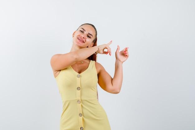 Jonge vrouw die in gele jurk naar de rechterbovenhoek wijst en vrolijk kijkt