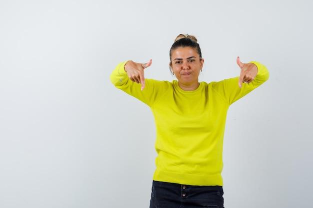 Jonge vrouw die in gele trui en zwarte broek naar beneden wijst en er serieus uitziet