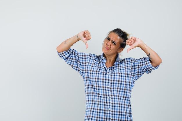 Jonge vrouw die in geruit overhemd duim toont en ontevreden kijkt.