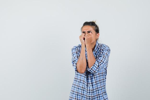 Jonge vrouw die in geruit overhemd gecombineerde vuisten opheft en verontrust kijkt.