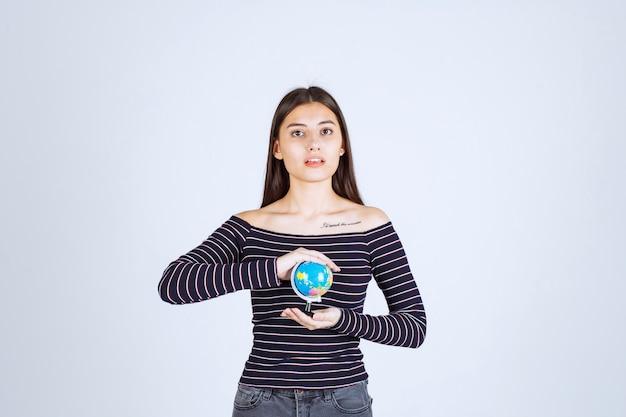Jonge vrouw die in gestreept overhemd een minibol tussen haar handen houdt