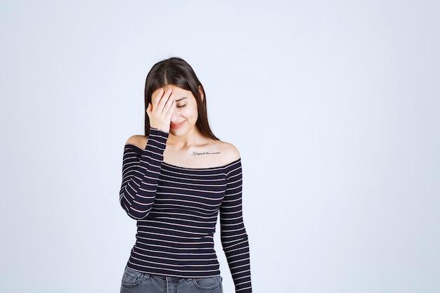 Jonge vrouw die in gestreept overhemd haar hoofd wegens hoofdpijn houdt