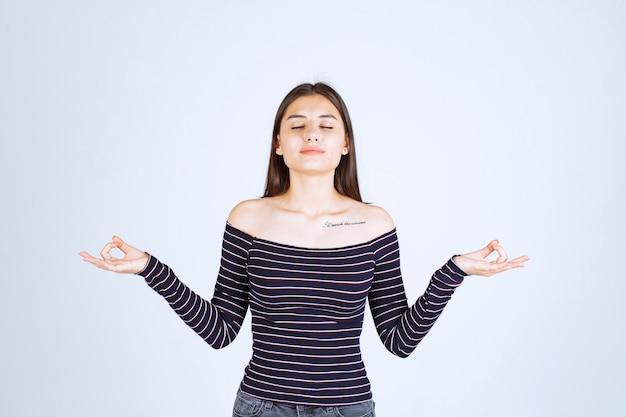 Jonge vrouw die in gestreept overhemd meditatie doet