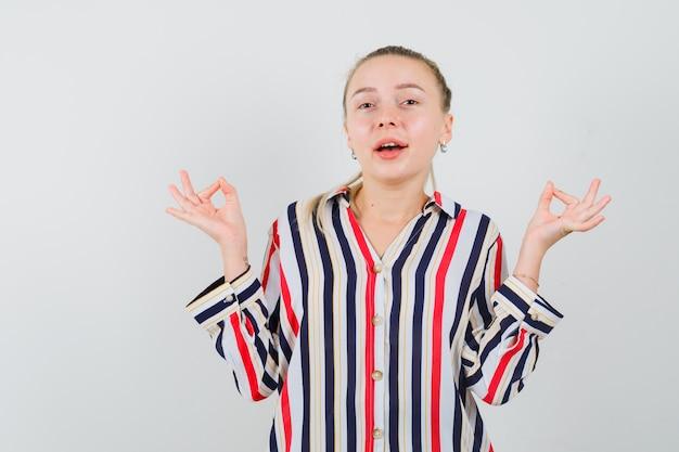 Jonge vrouw die in gestreepte blouse ok teken met beide handen toont en gelukkig kijkt