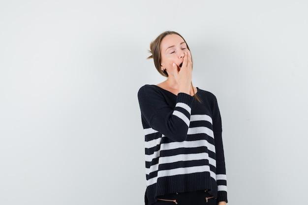 Jonge vrouw die in gestreepte breigoed en zwarte broek geeuwt en moe kijkt