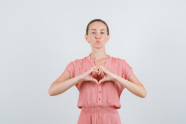 Jonge vrouw die in gestreepte kleding hartvorm met handen, vooraanzicht maakt.