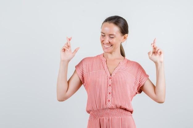 Jonge vrouw die in gestreepte kleding vingers gekruist houdt en vrolijk, vooraanzicht kijkt.