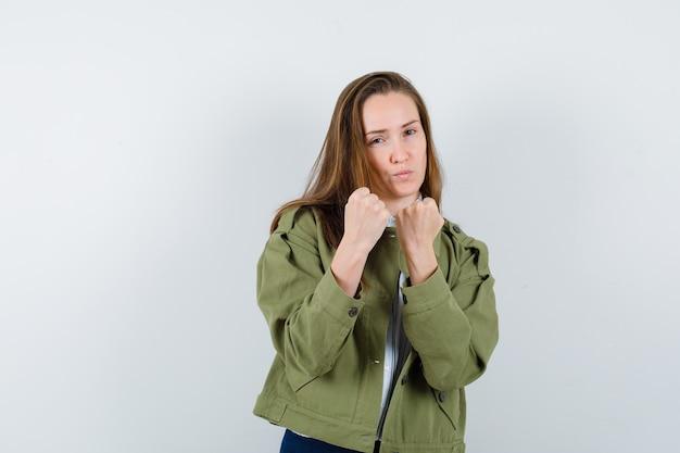 Jonge vrouw die in gevecht staat, poseert in shirt, jas en ziet er zelfverzekerd uit. vooraanzicht.