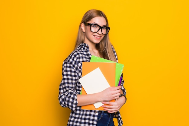 Jonge vrouw die in glazen boeken in zijn handen houdt en op een gele muur glimlacht. concept van studie, studenten