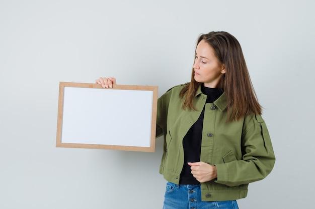 Jonge vrouw die in groen jasje leeg frame bekijkt en gericht, vooraanzicht kijkt.