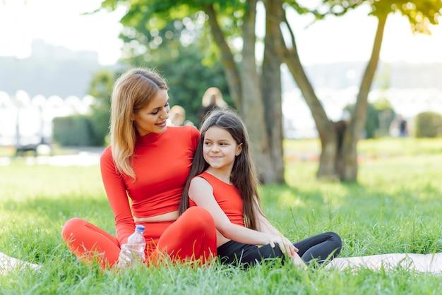 Jonge vrouw die in groen park met haar dochter rust