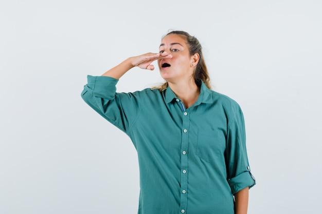 Jonge vrouw die in groene blouse probeert te niezen en gelukkig kijkt