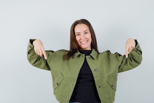 Jonge vrouw die in groene jas naar beneden wijst en tevreden kijkt. vooraanzicht.
