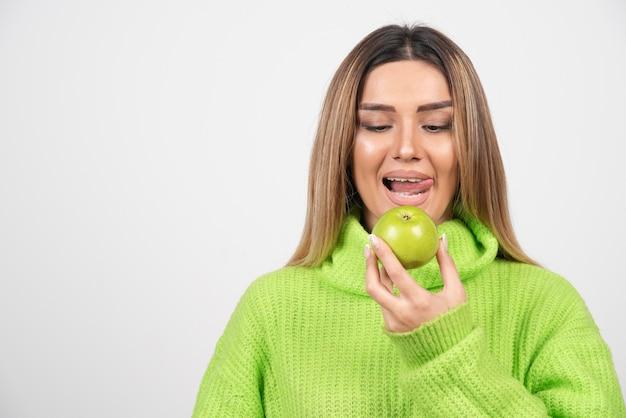 Jonge vrouw die in groene t-shirt een appel eet.