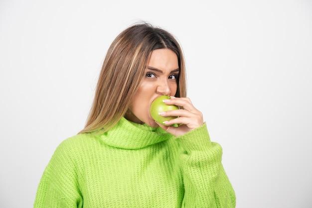 Jonge vrouw die in groene t-shirt een appel eet