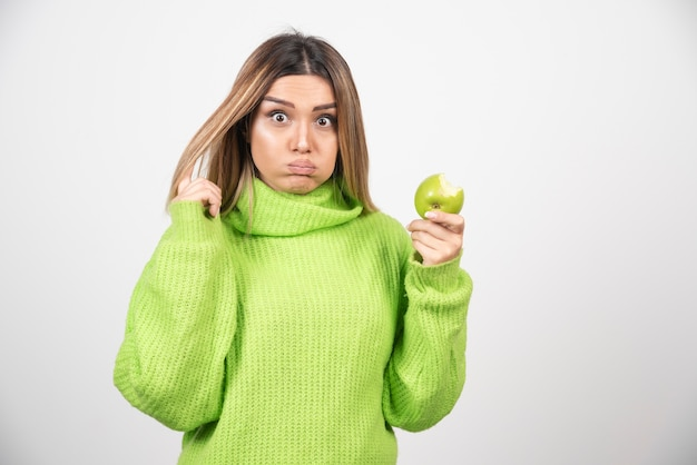 Jonge vrouw die in groene t-shirt een appel houdt.