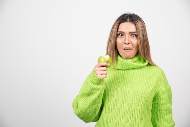 Jonge vrouw die in groene t-shirt een appel houdt