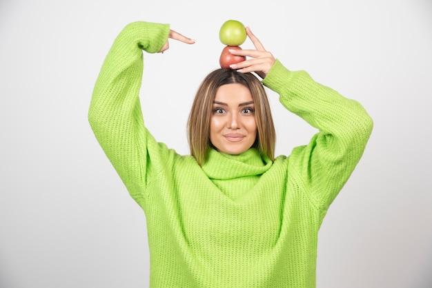Jonge vrouw die in groene t-shirt twee appels boven houdt.