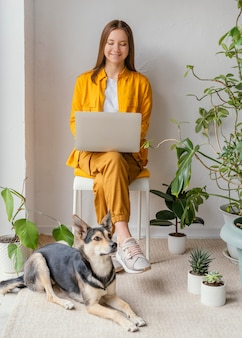 Jonge vrouw die in haar huistuin naast haar hond werkt